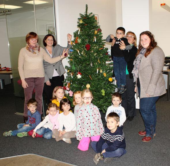 Kinder schmücken Tannenbaum in der Filiale Niederfeld